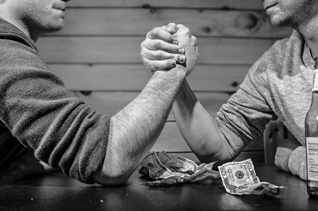 doi barbati care fac skanderbeg la o masa pe care sunt bani dezvoltare