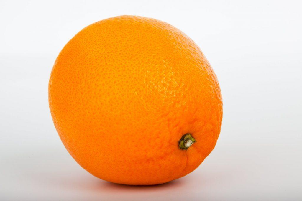 o portocala cu coaja pe fundal alb