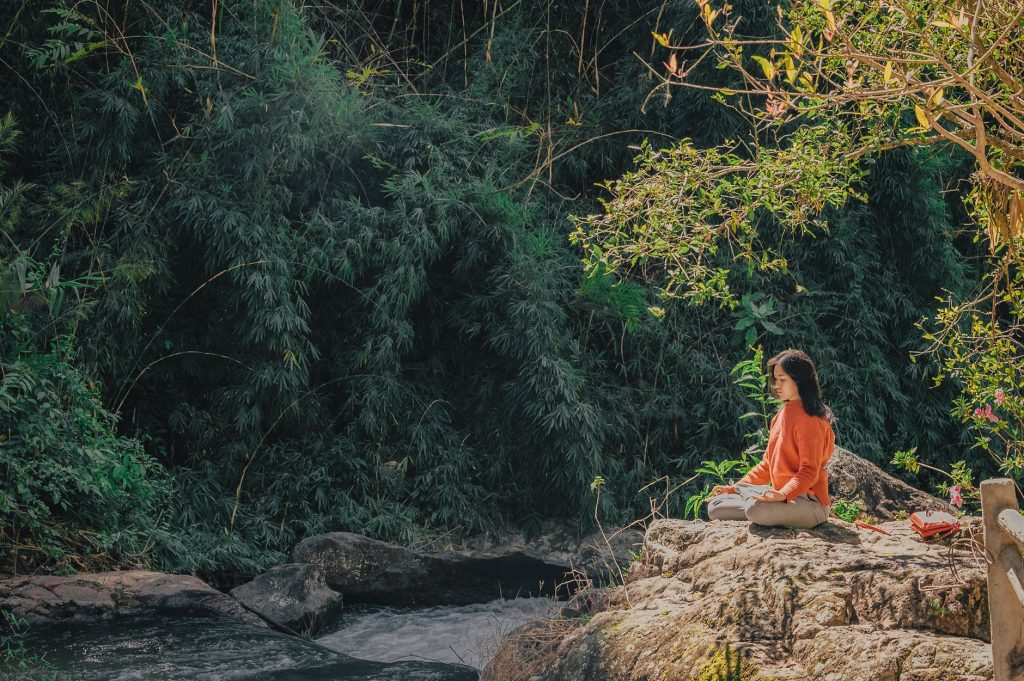 pace interioară femeie care mediteaza langa un rau dezvoltare