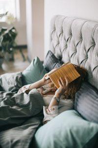 oboseala. femeia in pat cu cartea in mana