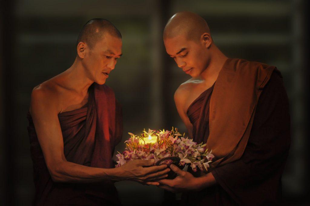 doi calugari tibetani care tin in mana o coroana de flori si o lumanare spiritualitate