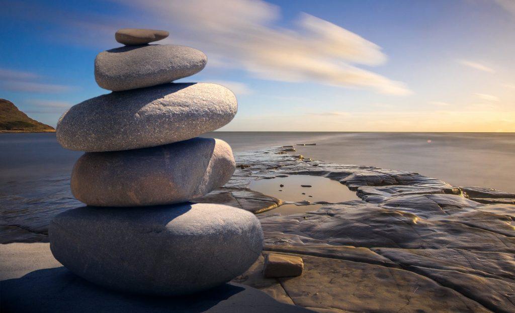 pietre zen asezate in echilibru pe malul marii